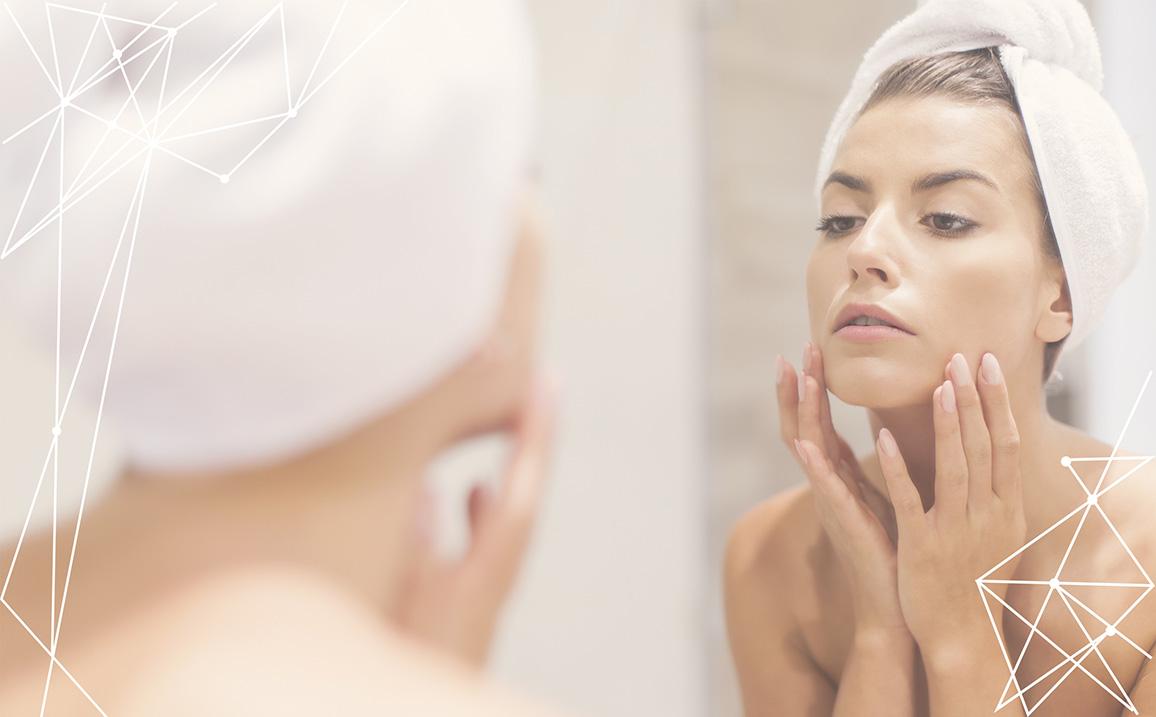 Donna allo specchio si spalma prodotti di bellezza: