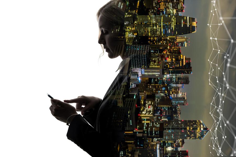 Donna con smartphone con 5G e dietro skyline cittadino notturno