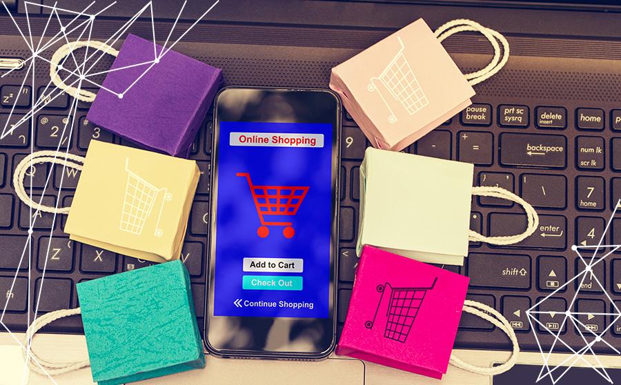 Smartphone e sacchetti regalo poggiati sulla tastiera di un pc