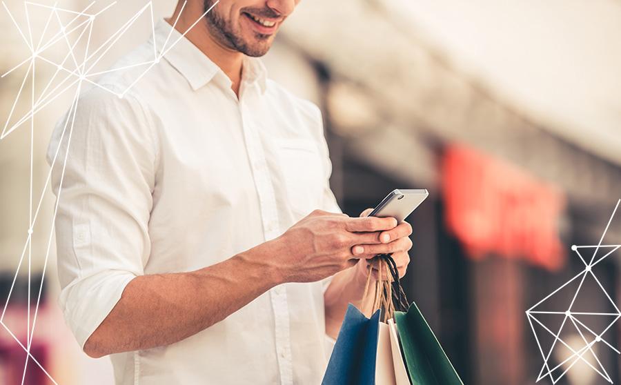 Giovane uomo tiene in mano uno smartphone e dei sacchetti per lo shopping, per rappresentare il customer engagement